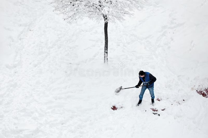 Male worker in uniform shoveling snow in the yard after a snowstorm in winter stock photo