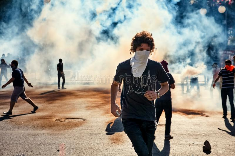 Male protester running away from the tear gas smoke fired by the police during Gezi park protests in Ankara, Turkey. Ankara, Turkey - June, 2013: Male protester stock photos