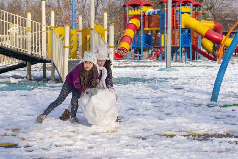 Ankara/Turkiet-Januari 01 2018: Två flickor rullar ett stort, och skurkrollen kastar snöboll för att bygga en snöman i en lekjord arkivbild