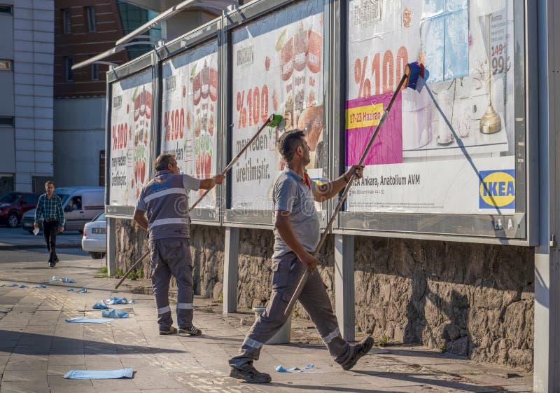 Ankara/Turkiet-Juni 23 2019: Arbetare att ta bort och installera annonsering på en affischtavla arkivfoton