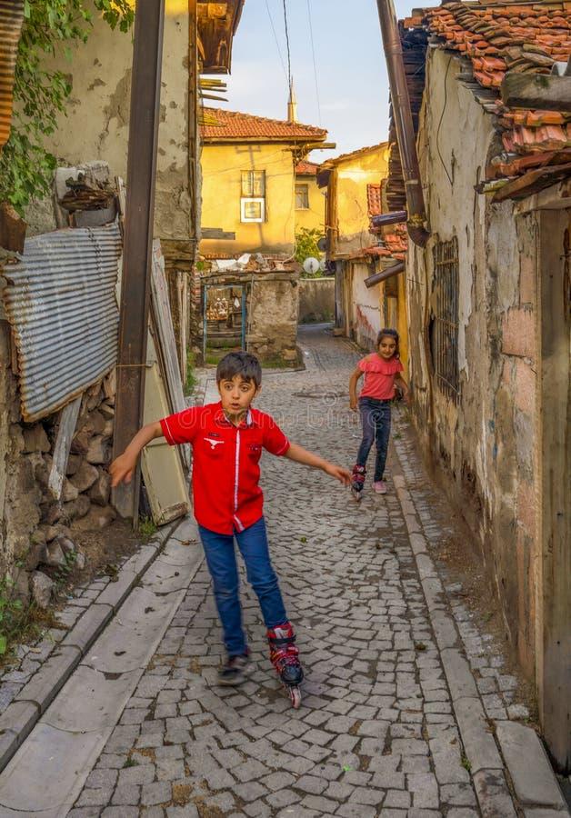 Ankara/Turkiet-Juni 16 2019: Barn som spelar med rullskridskon på gatan nära den Ankara slotten dela f?r begrepp Barnbruk arkivfoto