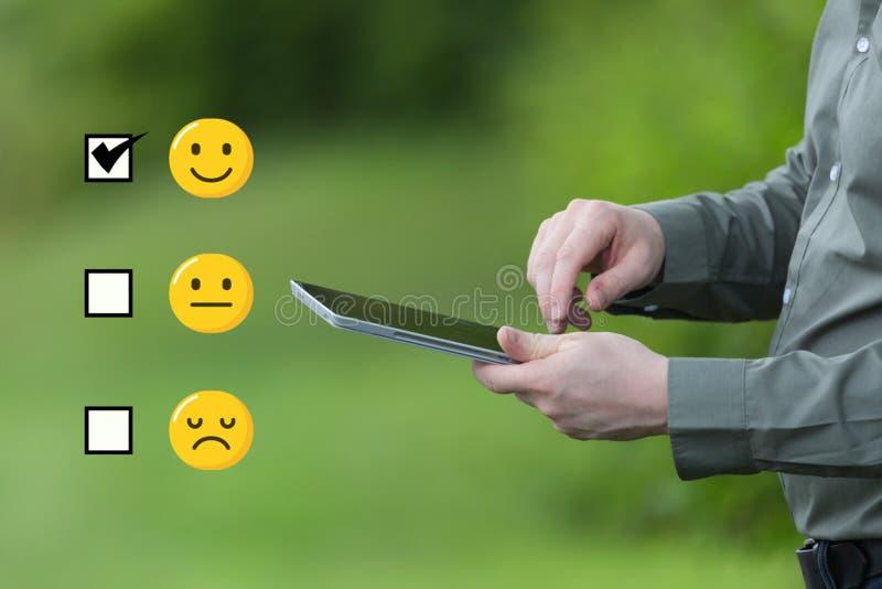 Ankiety pojęcie Biznesmen trzyma mądrze pastylkę mobilna na zielonym letnim dniu fotografia stock