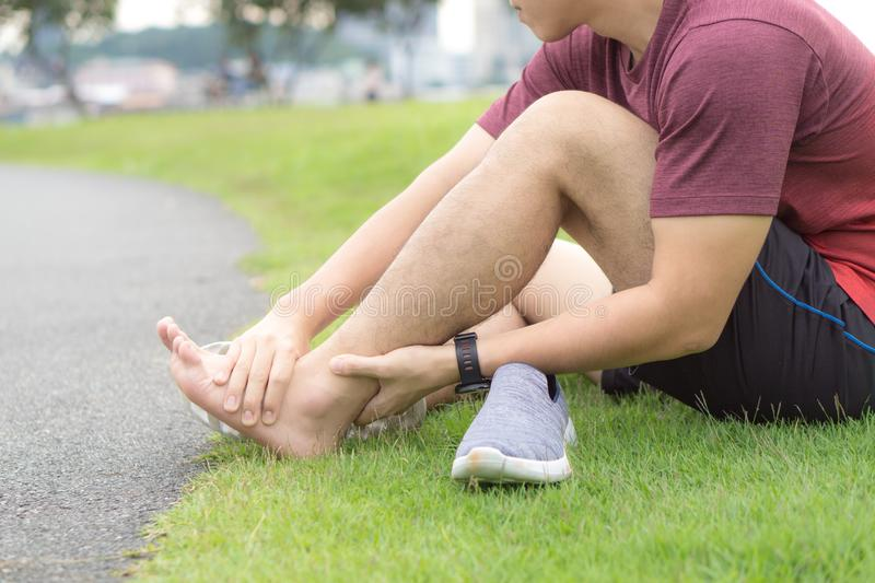 Ankle sprained. Young man suffering from an ankle injury while running at park. Healthcare and sport concept stock photo