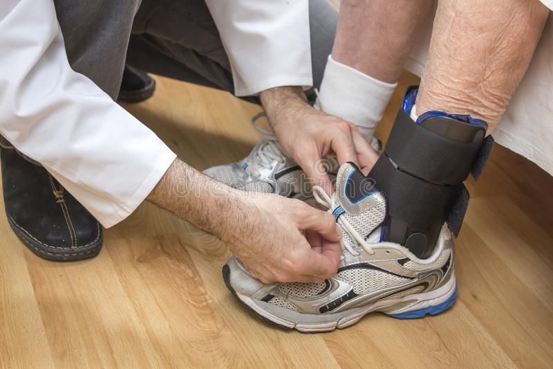 Ankle stabilizer placed on the leg of an old woman. The male nurse tyes the shoelace in the old woman`s shoe. stock photography