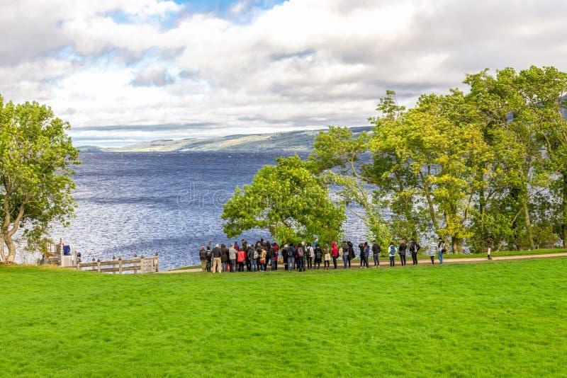 Ankunfts- und Abfahrtanlegestelle mit den Touristen, die auf das folgende Boot warten, um Urquhart-Schlossstandort, Schottland zu lizenzfreie stockfotos