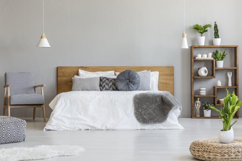 Anlage auf Puff im hellen Schlafzimmerinnenraum mit hölzernem Bett nahe bei kopiertem Lehnsessel Reales Foto lizenzfreie stockbilder