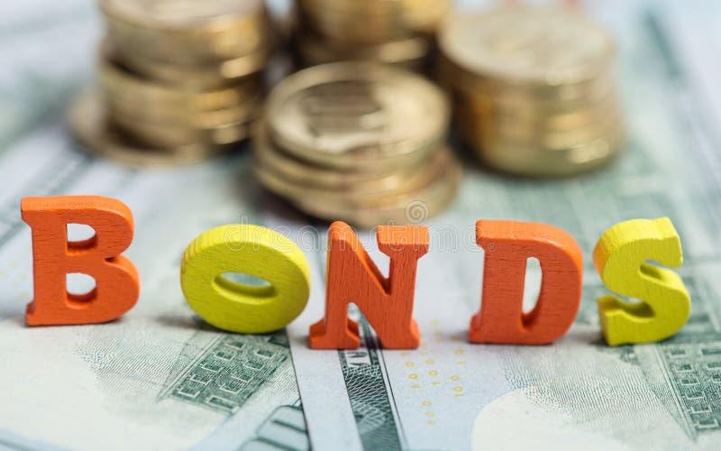Anlage in festverzinzlichen Anleihen an den hölzernen Buchstaben auf US-Dollar Rechnungen lizenzfreies stockbild