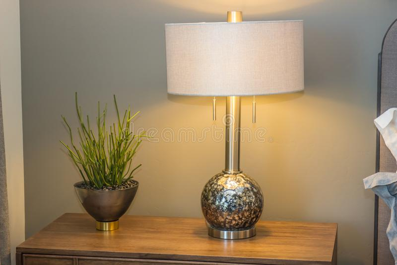 Anlage, Lampe u. Schatten auf Nightstand im modernen Schlafzimmer stockfotos