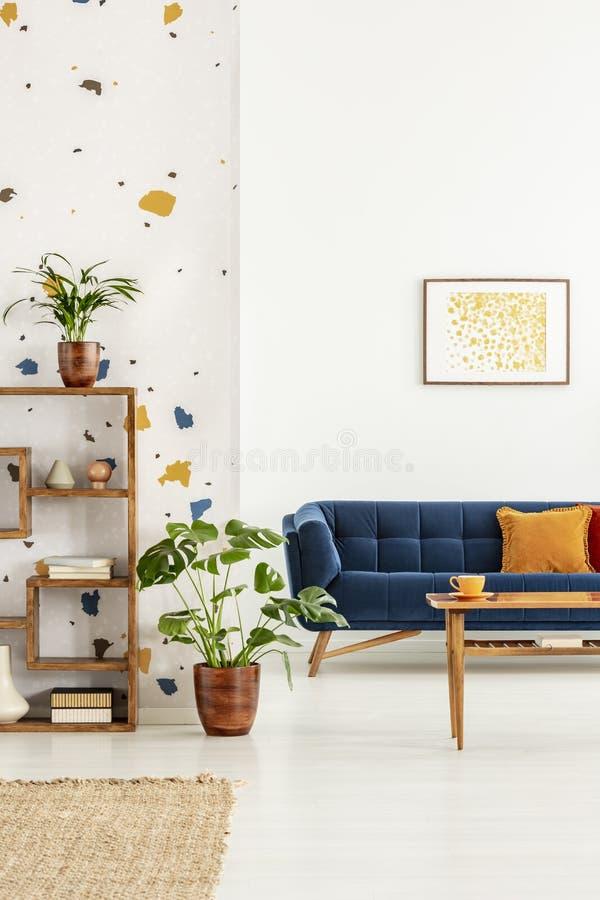 Anlagen im weißen Wohnungsinnenraum mit Plakat über blauem Sofa mit orange Kissen und Tabelle Reales Foto stockfoto