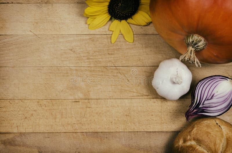 Anlagen und Gemüse auf Holztisch Kürbis mit Sonnenblume und Brot mit anderem Gemüse und Lebensmittel auf hölzernem Brett Lebensmi stockbilder