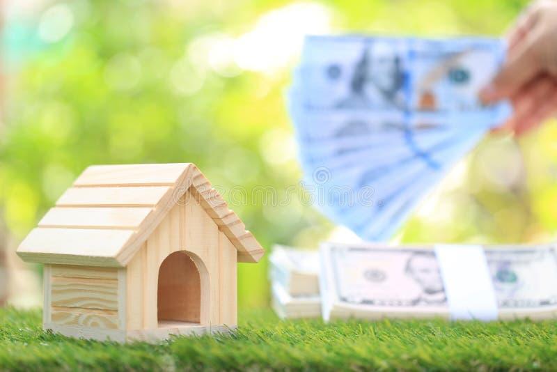 Anlagengeschäft und Immobilien, Musterhaus mit Banknote auf dem natürlichen grünen Hintergrund, speichernd für sich vorzubereiten stockbild