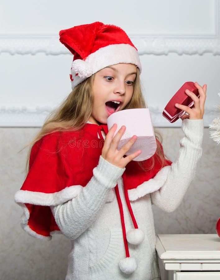 Anledningsbarn älskar jul Flickan firar den öppna gåvaasken för jul Jultomten kommer med hennes gåva Uppackning av julgåvan fotografering för bildbyråer