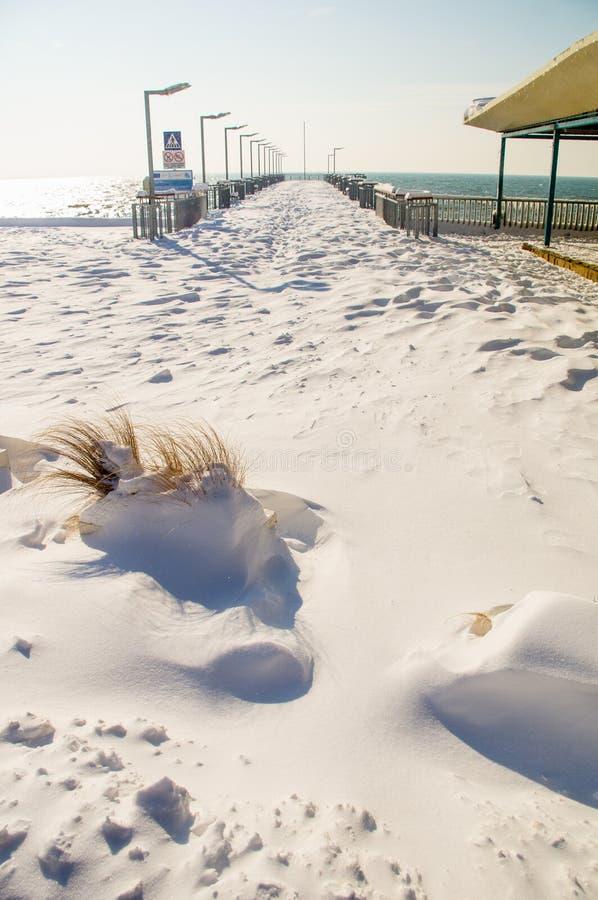 Anlegestelle auf einer schneebedeckten Promenade des Bulgaren Pomorie, Winter stockfoto