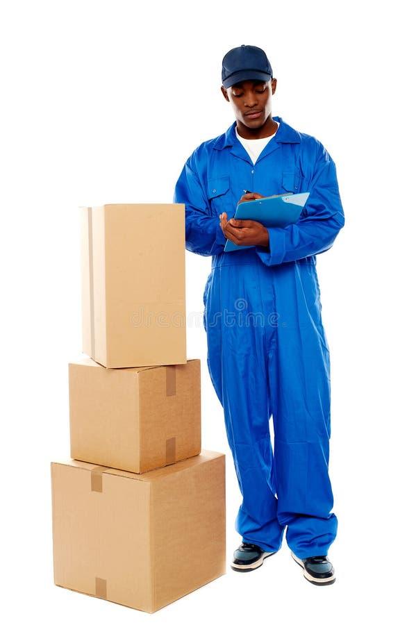 Anlieferungsjunge bei der Arbeit. Nehmen Sie bitte Ihre Waren an lizenzfreies stockfoto