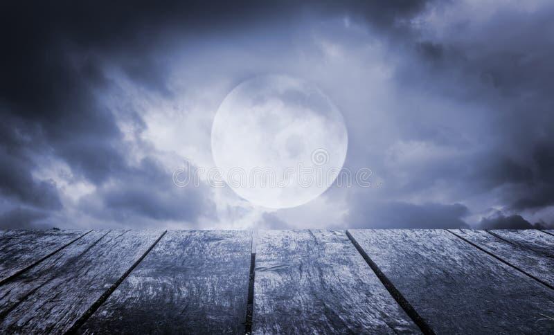 anmärkningar för bakgrundsslagträhalloween månsken Spöklik himmel med fullmånen och trätabellen royaltyfria foton
