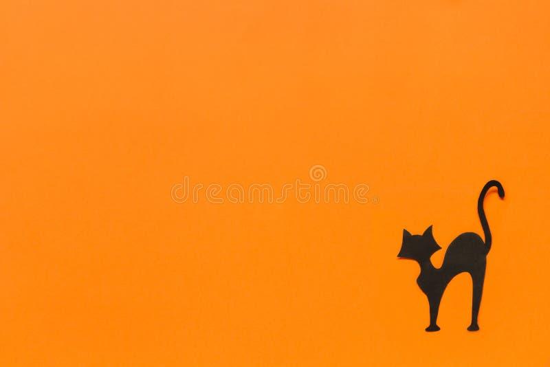 anmärkningar för bakgrundsslagträhalloween månsken Svart pappers- katt på orange bakgrund arkivfoton