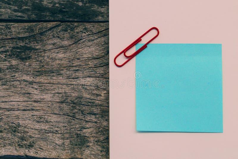 Anmärkningar för blått papper för färggemmar på gammal trätabellbackgroun royaltyfri bild