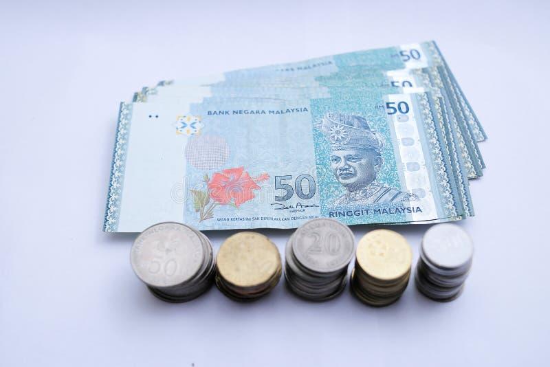 50 anm?rkningar f?r RinggitMalaysia pengar och malaysiskt mynt som isoleras p? vit bakgrund arkivbild
