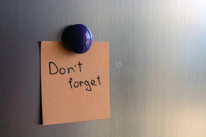 Anmärkningar med orden glömmer inte på dörrarna av kylskåpet arkivfoton