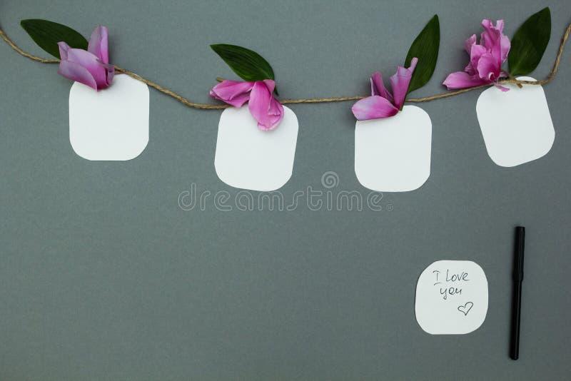 Anmärkningar på ett rep med blommor på en grå bakgrund, utrymme för text royaltyfri bild