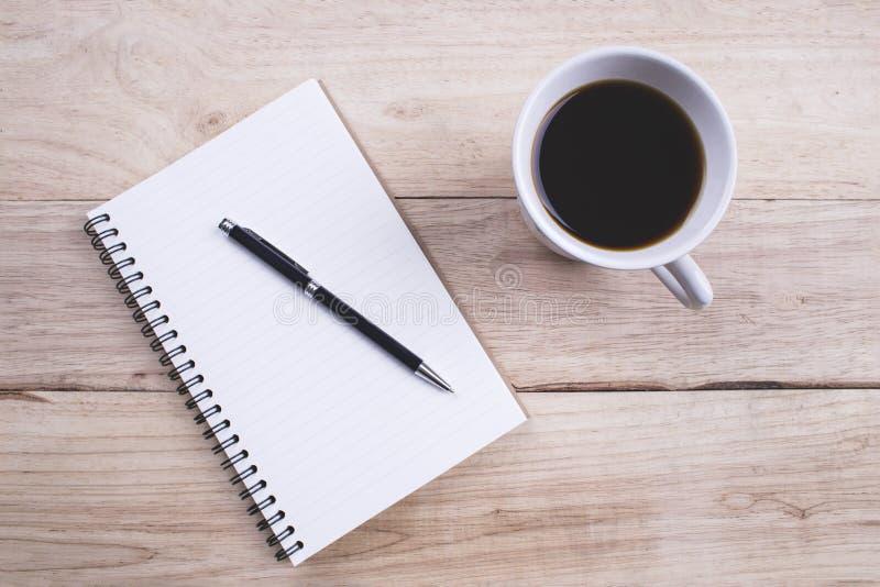 Anmärkningsbok för bästa sikt med pennan och en kopp kaffe på den wood tabellen fo royaltyfria bilder