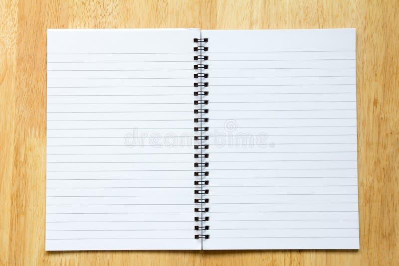 Anmärkningsbok för tomt papper på wood tabellbakgrund royaltyfri bild