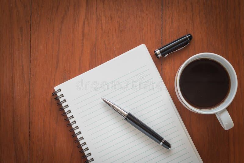 Anmärkningsbok med pennan och en kopp kaffe på den wood tabellen royaltyfri fotografi