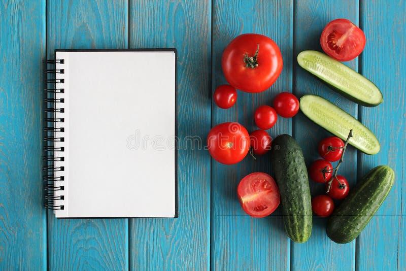 Anmärkningsbok och sammansättning av grönsaker på det blåa träskrivbordet royaltyfria foton
