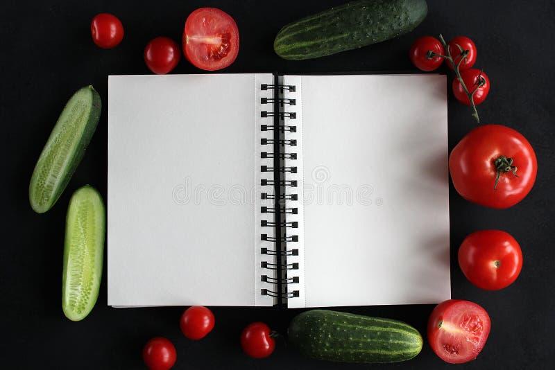 Anmärkningsbok och sammansättning av grönsaker på det svarta träskrivbordet royaltyfri fotografi