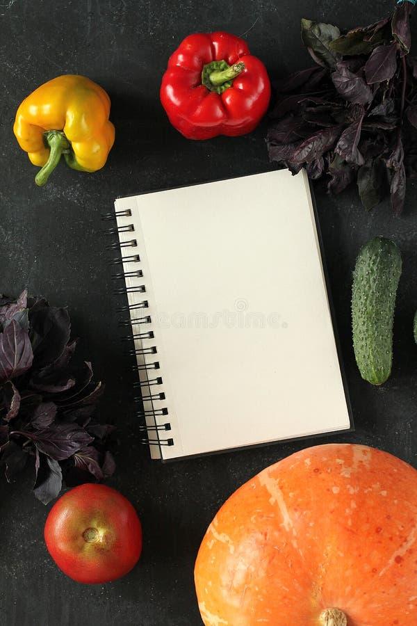 Anmärkningsbok och sammansättning av grönsaker på svart bräde fotografering för bildbyråer