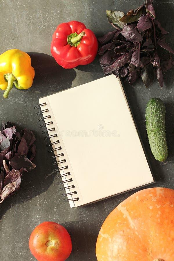 Anmärkningsbok och sammansättning av grönsaker på svart bräde royaltyfria bilder