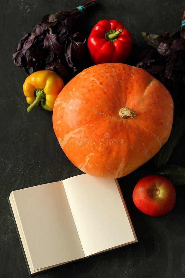 Anmärkningsbok och sammansättning av grönsaker på svart bräde royaltyfri fotografi