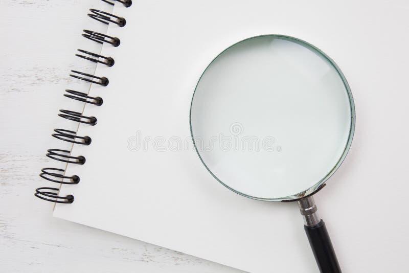 Anmärkningsbok på den vita tabellen med förstoringsglaset royaltyfria foton