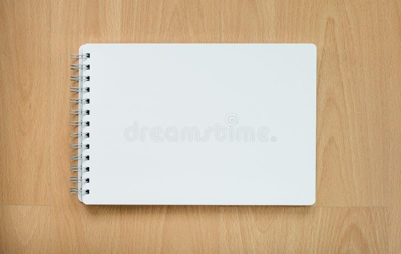 Anmärkningsbok på den wood tabellen fotografering för bildbyråer