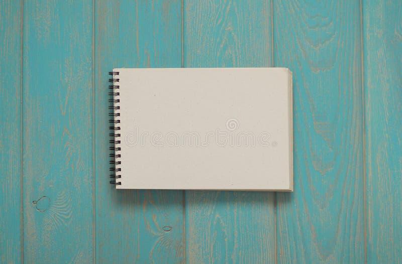 Anmärkningsbok på det blåa träskrivbordet royaltyfri fotografi