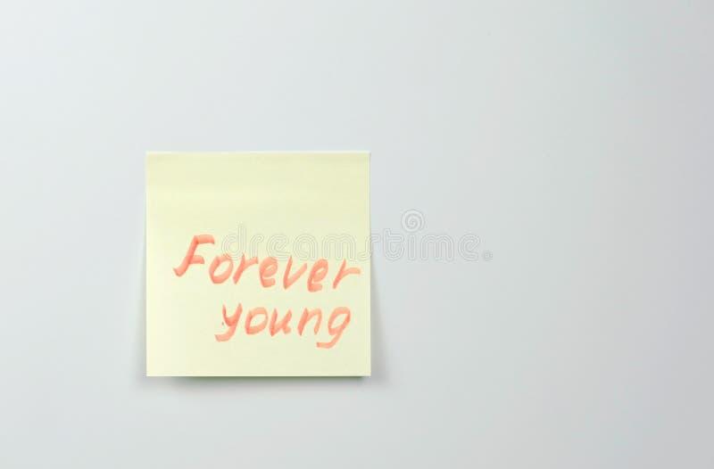 Anmerkung über gelbes Aufkleberpapier bedeckt mit Jungen der Motivationswörter für immer stockfotos