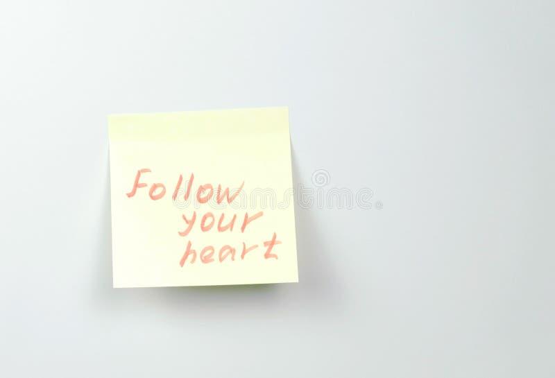 Anmerkung über Papierblätter des gelben Aufklebers mit Motivationswörtern folgen Ihrem Herzen stockfotos