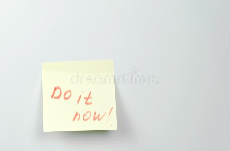 Anmerkung über Papierblätter des gelben Aufklebers mit Motivationswörtern tun es jetzt lizenzfreies stockbild