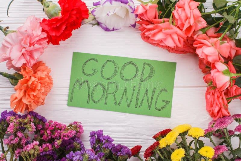 Anmerkung des gutenmorgens unter verschiedenen Blumen lizenzfreie stockfotos