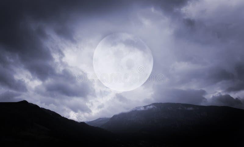 Anmerkungen und ein Baum in einem Mondschein Gespenstische Berge mit Vollmond stockfoto