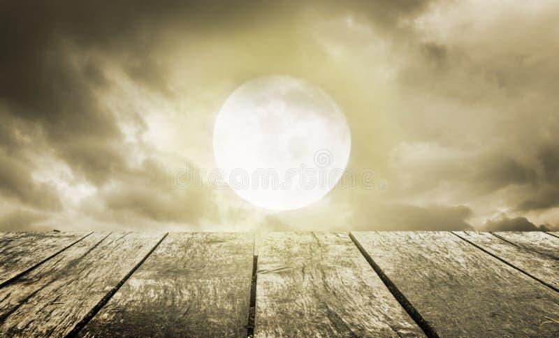Anmerkungen und ein Baum in einem Mondschein Gespenstischer Himmel mit Vollmond und Holztisch lizenzfreies stockfoto