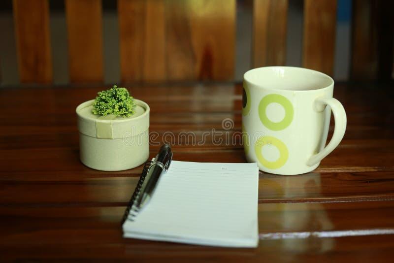 Anmerkungsbuch, Stift, eine Tasse Tee und Dekoration lokalisiert auf hölzernem Hintergrund stockfotos