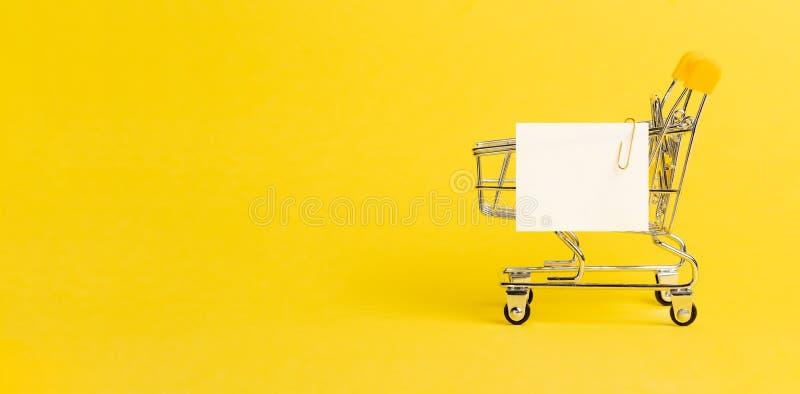 Anmerkungsliste des Einkaufswagens und des Weißbuches auf Gelb lizenzfreie stockfotos