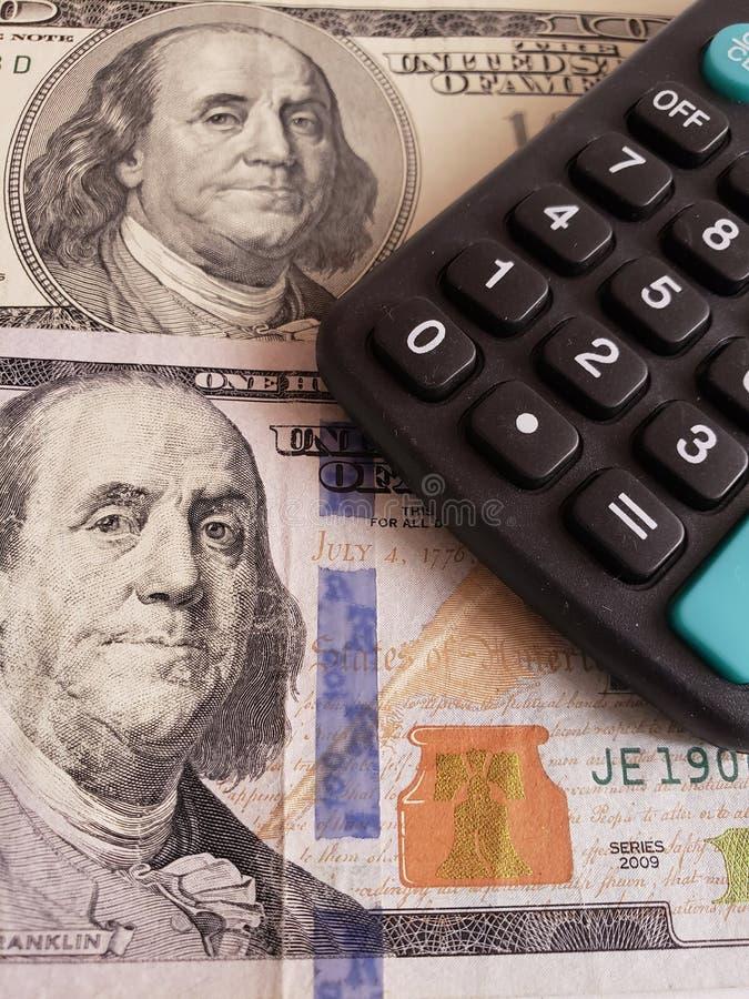Annäherung an Amerikaner 100 Dollarbanknoten von und Taschenrechner stockbild
