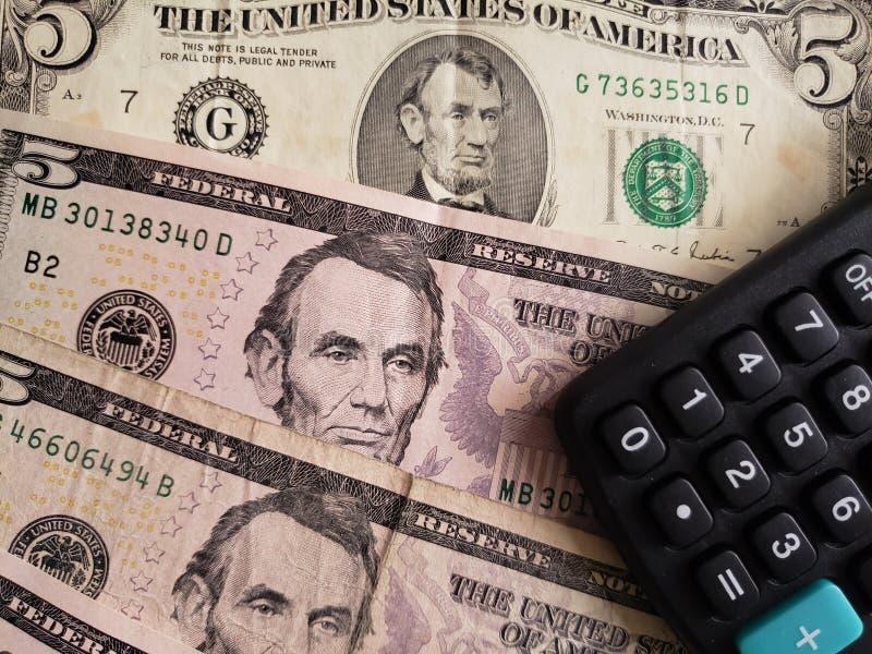 Annäherung an Amerikaner fünf Dollarbanknoten von und Taschenrechner lizenzfreie stockbilder