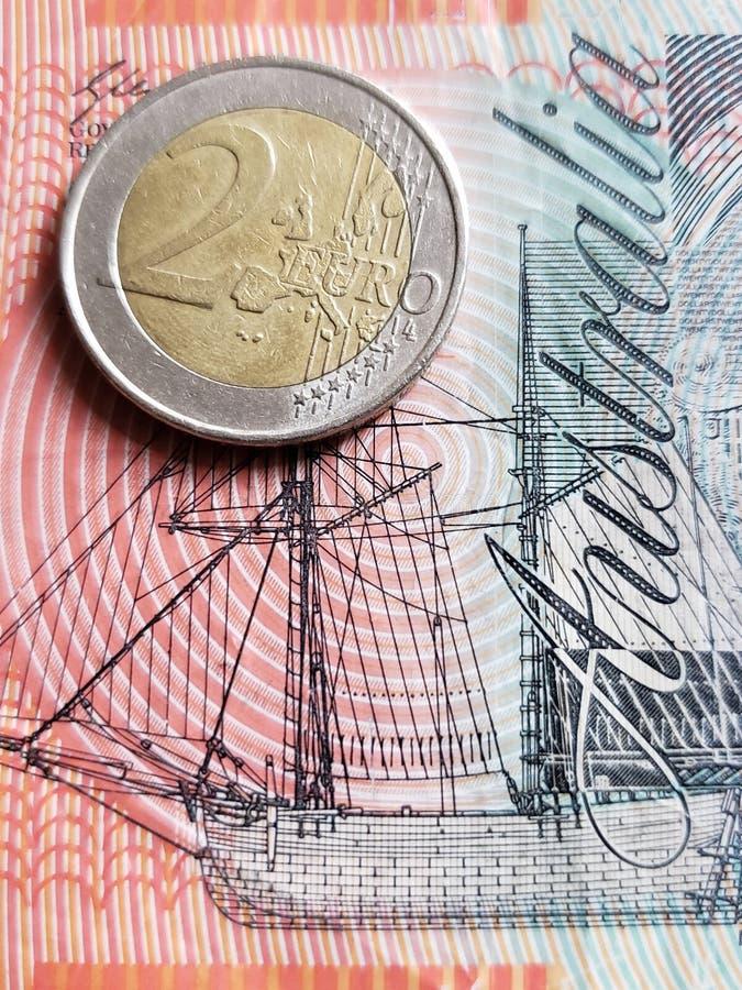 Annäherung an australische Banknote von zwei Dollar und Münze von 2 Euro, Hintergrund und Beschaffenheit lizenzfreies stockbild