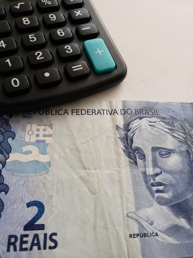 Annäherung an brasilianische Banknote von zwei Reais und von Taschenrechner lizenzfreie stockfotos
