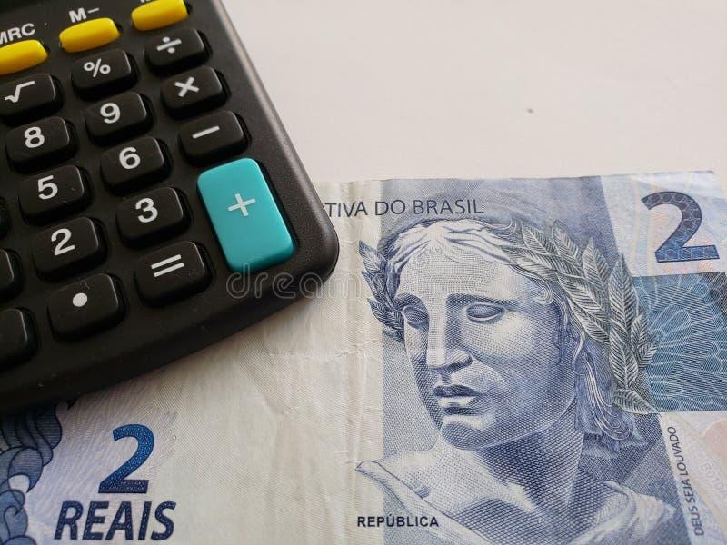 Annäherung an brasilianische Banknote von zwei Reais und von Taschenrechner stockfoto