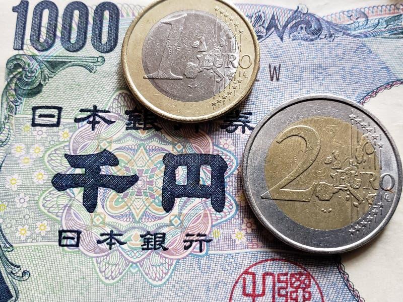 Annäherung an japanische Banknote von 1000 Yen- und Euromünzen, von Hintergrund und von Beschaffenheit lizenzfreie stockfotos