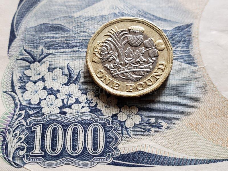 Annäherung an japanische Banknote von 1000 Yen und Münze von einem Sterlingpfund, von Hintergrund und von Beschaffenheit lizenzfreies stockbild